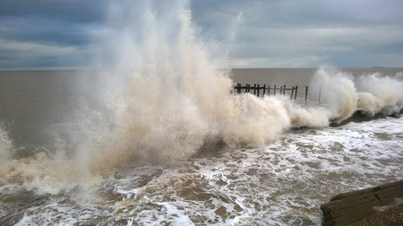 defenses: Large Seaspray of Winter tide on the coast by sea defenses Stock Photo