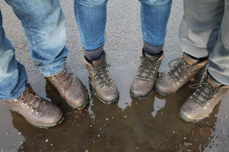 trouser legs: Three pairs of walking boots on a wet muddy day in the country Stock Photo