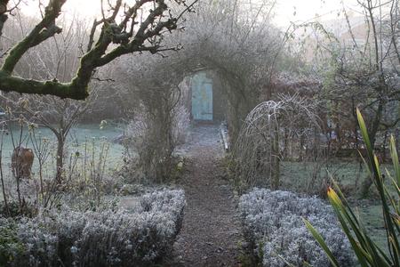 Eine Ansicht eines bereiften Wintergarten mit Weg zur Geheimtür führt