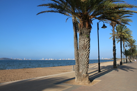 Beach view across the sandy beach on the promenade with palm trees and street lights, looking across the blue sea to La Manga Strip in the Cartegna region of Spain