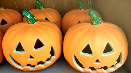 Close up of a group of halloween orange pumkins with crafted cut out faces and green stalks in Autumn or Fall on a shelf