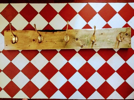Close up view of crafted vintage re cycled salvaged pine wood clothes rail hanger rail with Art Deco 1930ssolid brass hooks against a background of antique red white Victorian flagstone floor tiles Stock Photo