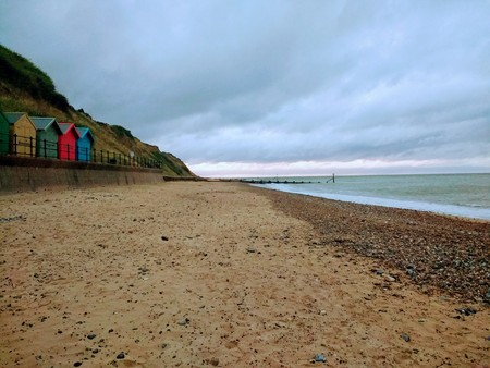 Seascape landscape of promenade walk along sandy beach with multi colour wood beach huts groyne sea waves and stormy grey blue skies on holiday in Mundesly Norfolk East Anglia England railing from the shore looking along coast 写真素材 - 106053296