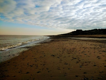 Landscape view of beautiful wild natural sandy vast beach at Winterton Norfolk East Anglia England with no people, tide out edge of ocean shore sand dunes into the horizon, blue sky in cool December Stock Photo