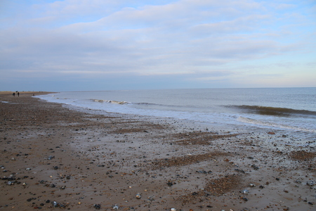 Stunning natural vast landscape view over ocean at sundown sunset on sandy beach with pebbles no people looking out to horizon over calm tide with blue pink tranquil skies in Autumn in Norfolk East Anglia England