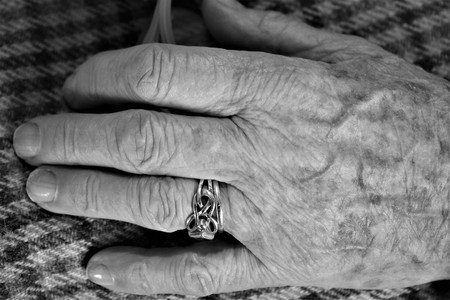 Black and white close up of pair of elderly female small hand with wedding ring with check material of skirt of seated figure