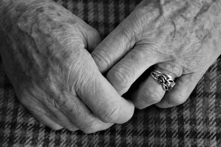 Black and white close up of pair of elderly female small hands clasped together showing aging skin of senior with fingers and wedding and engagement ring with check material of skirt of seated figure