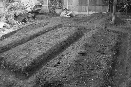 Black and white Landscape view of trenches dug for foundations of garden hut or studio shed building outdoors in the cleared earth with straight line dug out pathways ready for brick structure prior to shed construct