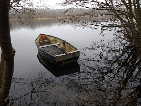 beautiful tranquil scene of Norfolk Broad rowing boat on water landscape with still lake surroundings of bare winter trees brown branches and grey icy misty skies with foliage reflected in water