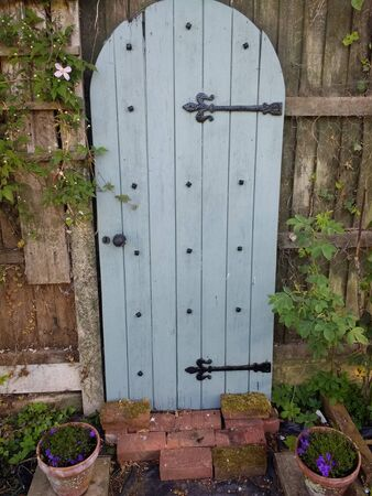 Landscape showing secret garden antique aged rustic door with blue green paint and black metal hinges at end of path by fencing with clematis flower growing at side and plant pots in rural Norfolk Фото со стока