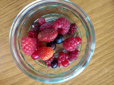 Close up view from above of raspberries, strawberries, blackcurrants and red currants in glass dish, the organic fruit freshly picked from rural English allotment garden orchard in Summer Фото со стока
