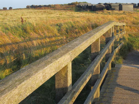 Summer Landscape at Walberswick near Southwold in Suffolk East Anglia from the wooden bridge that leads to the campsite and stony beach with huts by the sand dunes over the reeds and blue sky