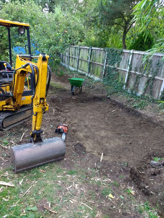 Yellow digger heavy motor machinery with digging arm moving earth, re-landscaping an organic garden lawn orchard area moving the soil to create level ground in outdoor growing space with trees & fence Reklamní fotografie