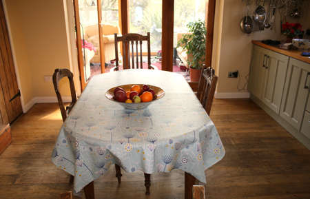 Interior view of wood kitchen with oak floors, large table cover floral oil cloth with gold bowl of fruit, oranges, apples in centre and cream room walls and glass folding doors to conservatory day