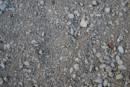 Close up of type 1 mortar base crushed concrete stones with some brick granite gravel mix on ground in garden landscape for build of constructing wooden shed base