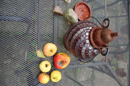 Close up of still life objects of mosaic glass metal lantern light, windfall Autumn apples, stones and earthenware pot sat on wire mesh table in garden on patio seating outdoors in Winter in grey cold