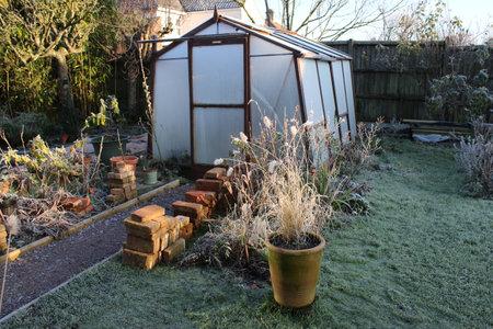 Landscape of frozen Winter garden in heavy white frost with misty pane glass greenhouse, icy lawn beside path and plants pots trees in Winter freeze seasonal frosty weather in Norfolk England