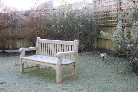 Garden ;landscape of back border showing wooden bare fence and trellis with large teak bench sat on grass lawn, rose trees growing upwards white icy frost Winter day in Norfolk England with no people