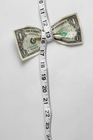 Dollar being squeezed by measuring tape.
