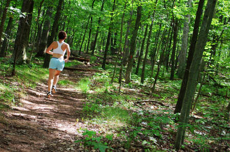 Mature woman running in forest. Stock Photo
