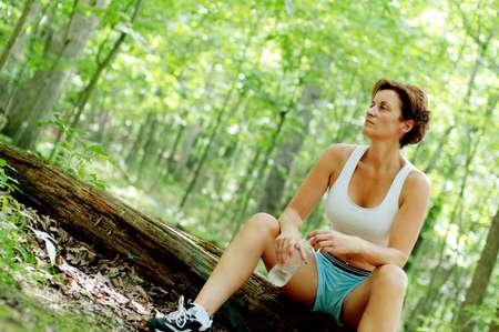 成熟した女性ランナーが森の中で休憩します。