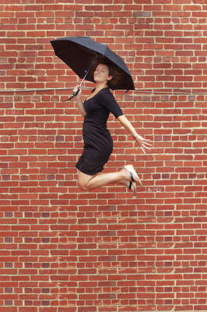 unrealistic: Lady jumping with umbrella high into air. Stock Photo