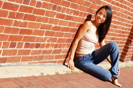 Modieuze jonge vrouw tegen rode bak stenen muur.