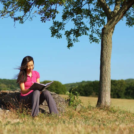 person writing: Girl writing in notebook in a field. Stock Photo
