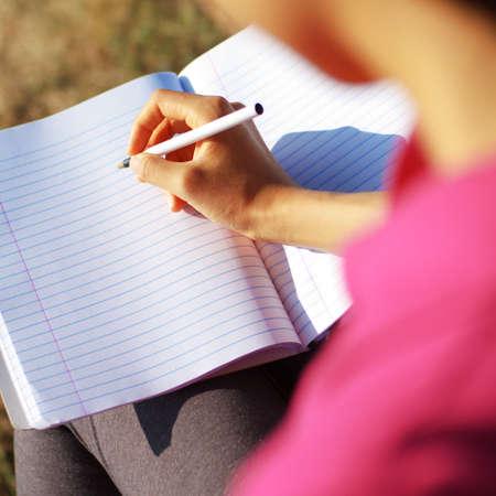 persona escribiendo: Chica en la escritura en un cuaderno de campo.