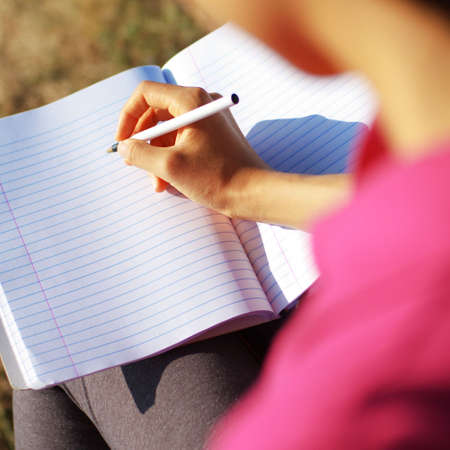 composition book: Girl writing in notebook in a field. Stock Photo