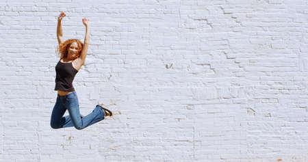 Attractive urban girl against white brick wall.