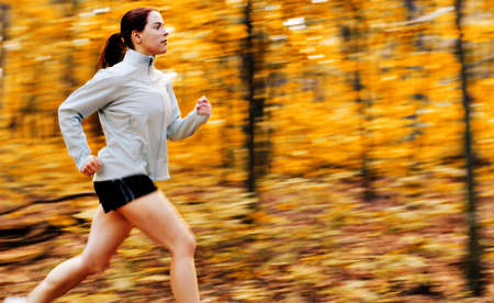 girl in shorts: Beautiful young woman running in a fall forest. Stock Photo