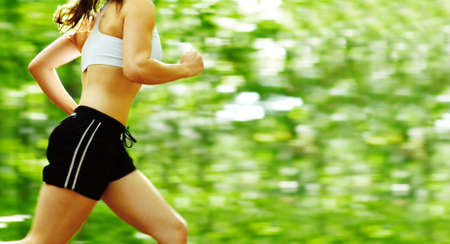 Endurance: Beautiful young woman runner in a green forest. Stock Photo