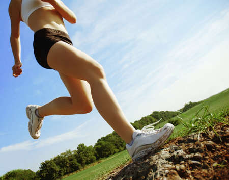 Beautiful woman runner in front of blue sky, low angle. Stock Photo