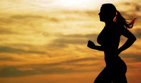 sun track: Beautiful young woman running in front of a sunset.