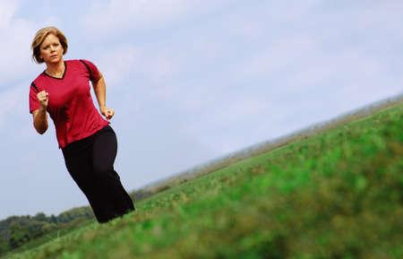Mature woman jogging in a big summer field.