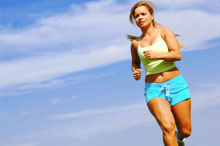 Beautiful young woman running against blue sky. Stock Photo