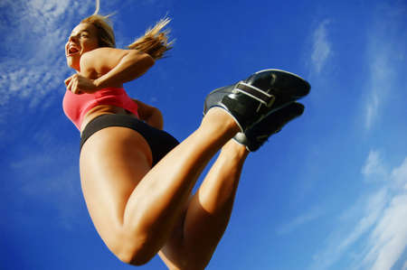 Beautiful woman leaping into air against sky, low angle.
