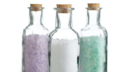 Colored bath salt against a white background.