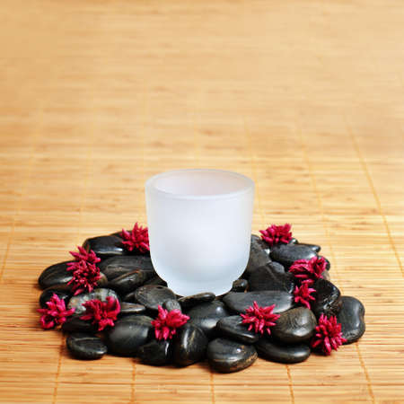 revitalize: Cup on rocks on top of bamboo.