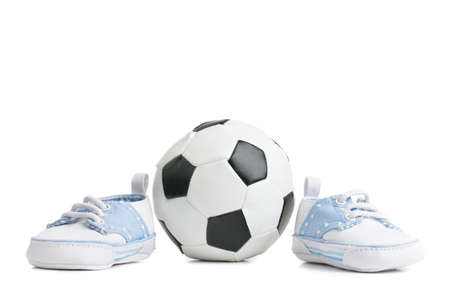 A football  soccer ball with baby shoes, on white.