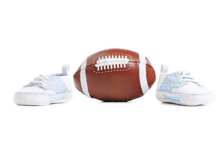 Football with baby shoes against a white background.