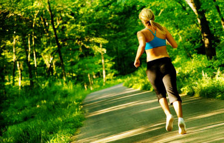 athletic activity: Young woman working out on a forest path.