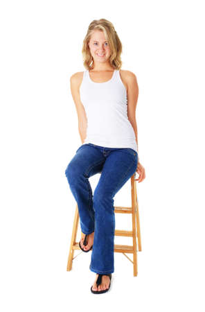 tang: Casual young woman sitting on a small ladder agaisnt white.
