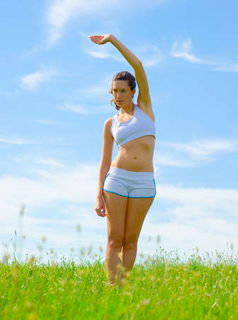 Mature woman athlete practicing in a spring meadow, from a complete series. Stock Photo - 5480760
