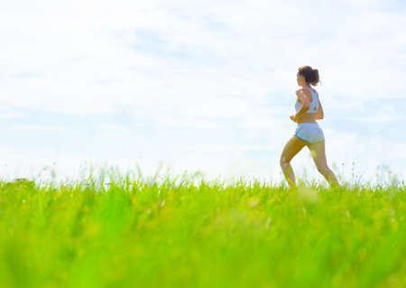 Volwassen vrouw atleet beoefenen in een weide van de lente, van een complete serie.  Stockfoto