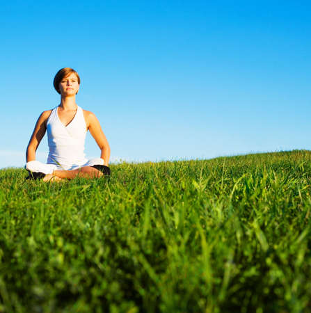 Young woman doing yoga in a sunny meadow, from a complete series of photos. photo