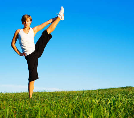 Young woman doing yoga in a sunny meadow, from a complete series of photos. Stock fotó
