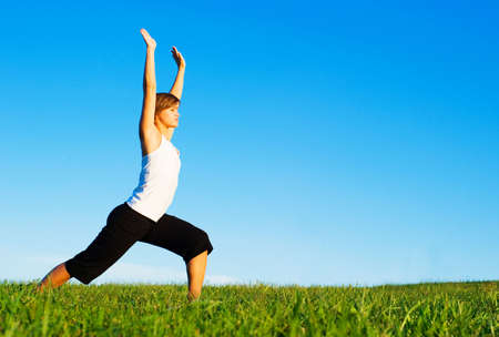 Young woman doing yoga in a sunny meadow, from a complete series of photos. Standard-Bild