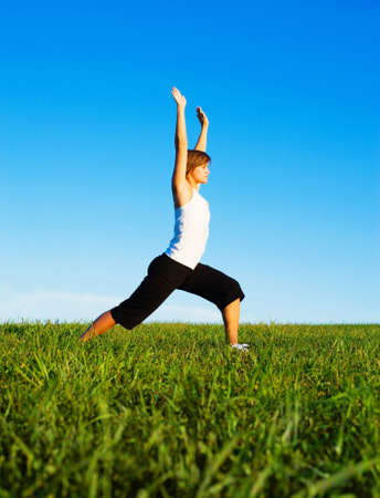 Young woman doing yoga in a sunny meadow, from a complete series of photos. Stock Photo - 5640641